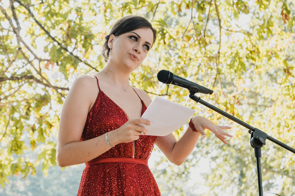 Young woman reading a speech - Stock Photo - Images