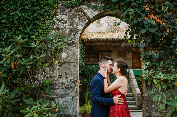 Elegant young couple on a luxurious building with vegetation - Stock Photo - Images