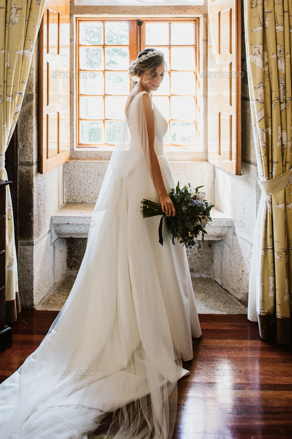 Bride on her wedding dress in front of a window - Stock Photo - Images