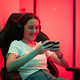 Cybersport gamer playing mobile game on the smart phone sitting on a gaming chair in neon color room - PhotoDune Item for Sale