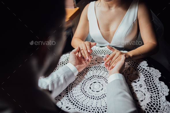 guy in a suit and a girl in a dress are sitting at the table and holding hands - Stock Photo - Images