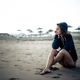 Cute lonely caucasian young girl sitting at the beach on the sand looking the open space - PhotoDune Item for Sale