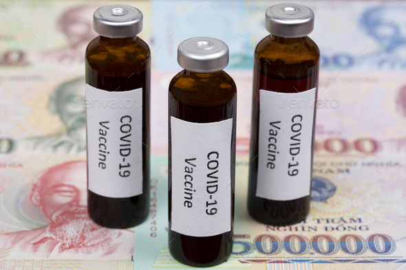 Vaccine against Covid-19 on the background of Vietnamese money - Stock Photo - Images