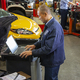 Pacific Islander mechanic typing on a laptop while co-workers work on cars in background - PhotoDune Item for Sale