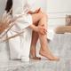 Young brunette woman applying body scrub or cream on skin sitting in luxury bathroom - PhotoDune Item for Sale