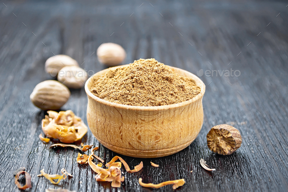 Nutmeg round in bowl on wooden board - Stock Photo - Images
