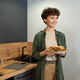 Happy young brunette woman in casualwear carrying plate with homemade sandwiches - PhotoDune Item for Sale