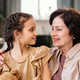 Affectionate mature brunette woman embracing her cute little granddaughter - PhotoDune Item for Sale