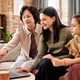 Three generation family of females in casualwear sitting in front of laptop - PhotoDune Item for Sale
