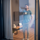 Young bearded man holding mug with hot drink and looking through large window - PhotoDune Item for Sale