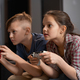 Cute serious siblings sitting on couch in front of tv set and playing video game - PhotoDune Item for Sale