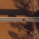 Aerial view of single red car crossing the bridge across the river - PhotoDune Item for Sale