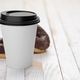 Disposable coffee paper cup with donuts on white wooden plank tabletop. - PhotoDune Item for Sale