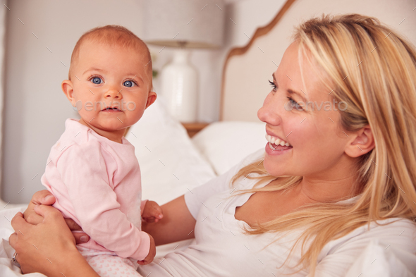 Loving Mother In Bed Playing Game With Baby Daughter Wearing Pyjamas - Stock Photo - Images