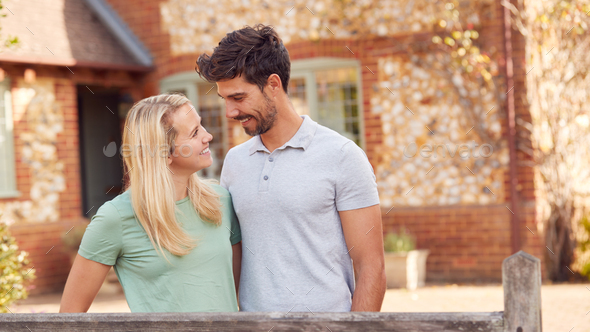 Portrait Of Smiling Couple Standing By Gate Outside Home In Countryside Together - Stock Photo - Images