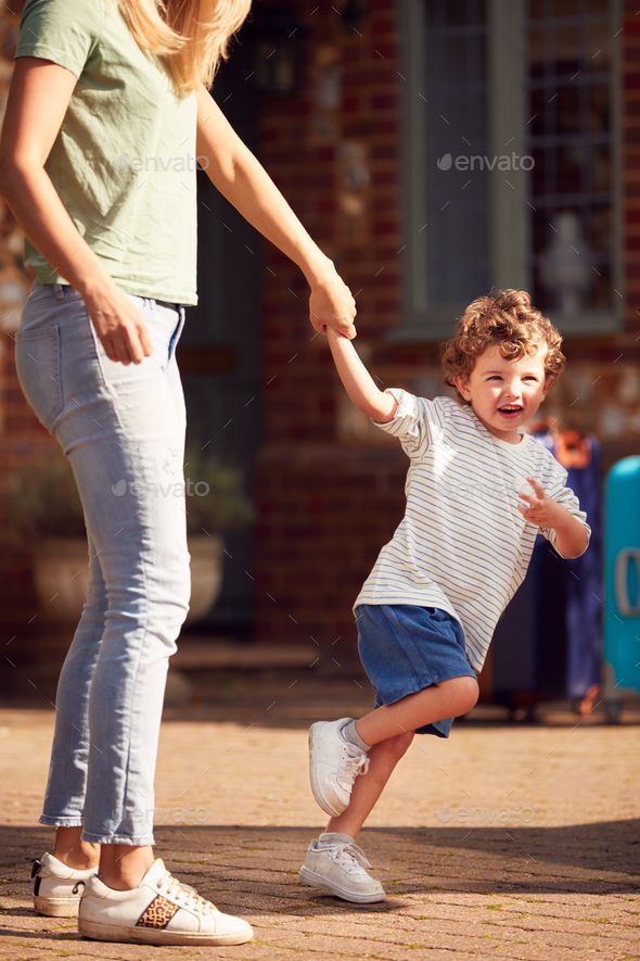 Young Boy Holding Mothers Hand Outside House As They Leave For Family Vacation - Stock Photo - Images