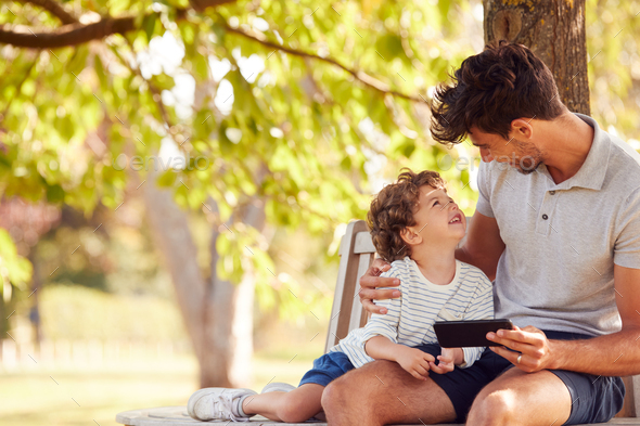Father Sitting On Park Bench Under Tree With Son Looking At Mobile Phone Together - Stock Photo - Images