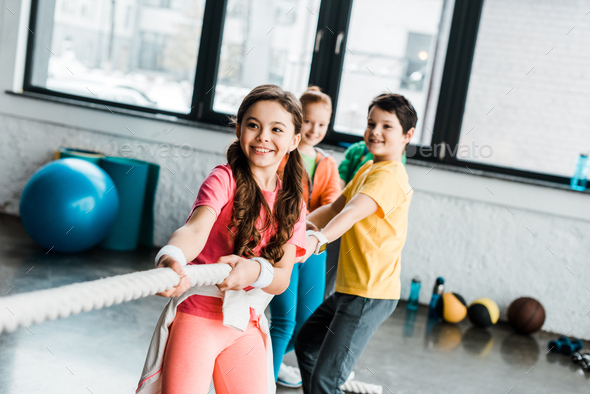 Smiling kids in sportswear pulling rope in gym - Stock Photo - Images