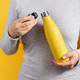 Woman in grey tee holding yellow insulated bottle on yellow background - PhotoDune Item for Sale