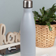 Grey insulated bottle on white desk surrounded by modern gadgets and plant - PhotoDune Item for Sale
