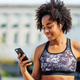 Athletic woman using her mobile phone outdoors. - PhotoDune Item for Sale
