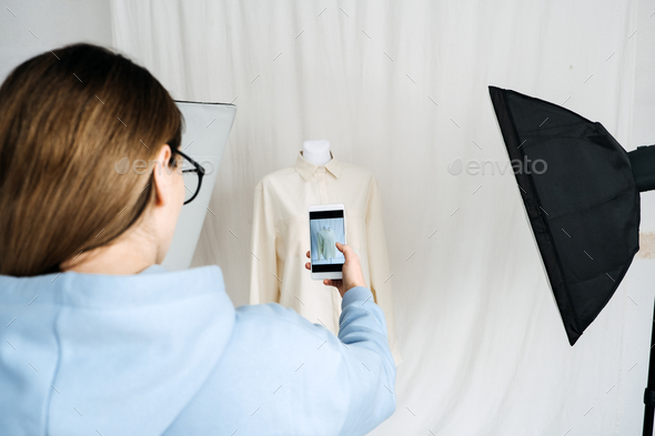AR VR Technology in Fashion Industry. Female designer shotting clothes on mannequin by cell phone - Stock Photo - Images