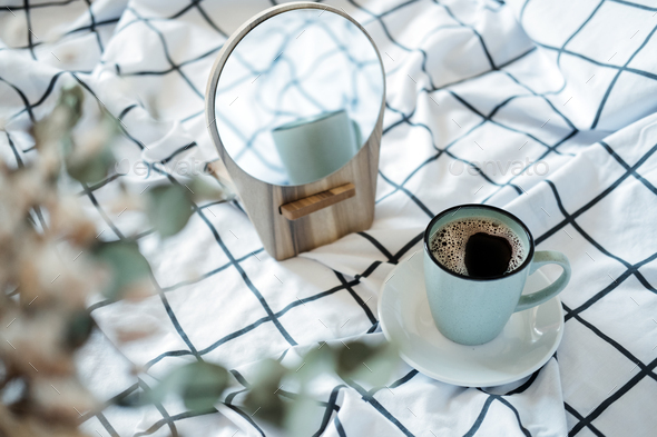 Morning cozy mood. Coffee in the bed. A cup of black coffee in bed on white checkered blanket - Stock Photo - Images