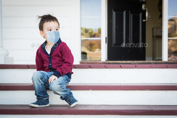 Melancholy Mixed Race Boy On Front Porch Wearing Medical Face Mask - Stock Photo - Images