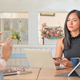 Young woman holds a smartphone in hand and laptop with tablet on the table. - PhotoDune Item for Sale