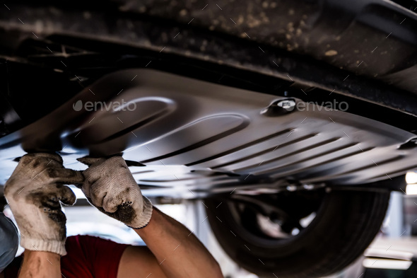 Car mechanic checks engine protection on Service station - Stock Photo - Images