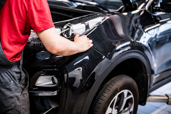 Male car mechanic at autosalon hands on black car business class at autoservice - Stock Photo - Images