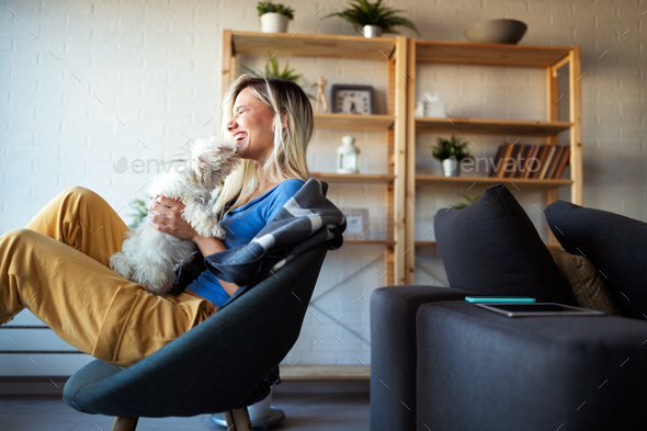 Portrait of beautiful young woman with dog playing at home - Stock Photo - Images