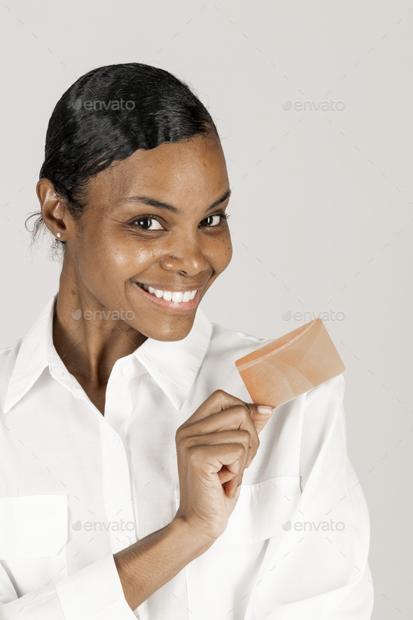 Happy black woman holding a credit card in hand - Stock Photo - Images