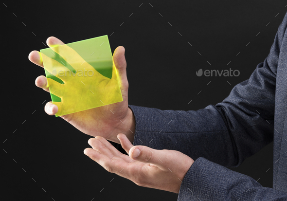 Businessman holding yellow hologram plate - Stock Photo - Images
