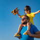 Father and son playing against blue summer sky background - PhotoDune Item for Sale