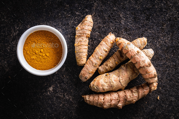 Indian turmeric powder and root. Turmeric spice. Ground turmeric. - Stock Photo - Images