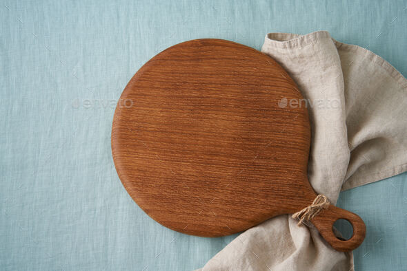 Food background mockup with round wooden cutting board on blue linen textile tablecloth. Placeit - Stock Photo - Images