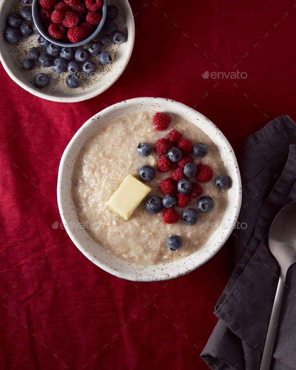 Oatmeal porridge with blueberry, bilberry. Breakfast in white bowl with fresh berries, vertical - Stock Photo - Images