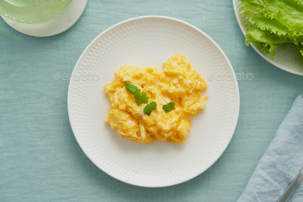 Scrambled eggs, omelette. Breakfast with pan-fried eggs. Texture of omelet on white plate - Stock Photo - Images