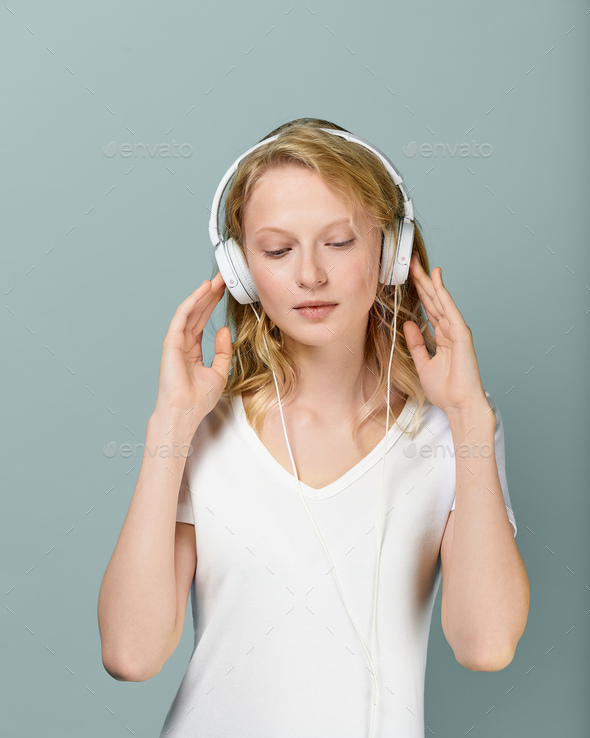 Placeit. Closeup portrait of young woman closed eyes listening music via headphones on color neutral - Stock Photo - Images