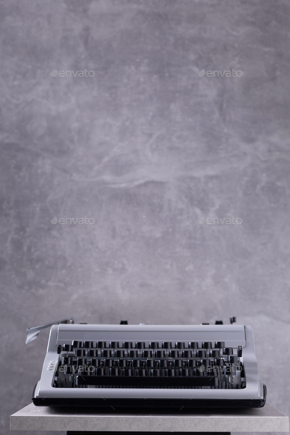Vintage typewriter at wooden top table or shelf near wall background surface - Stock Photo - Images