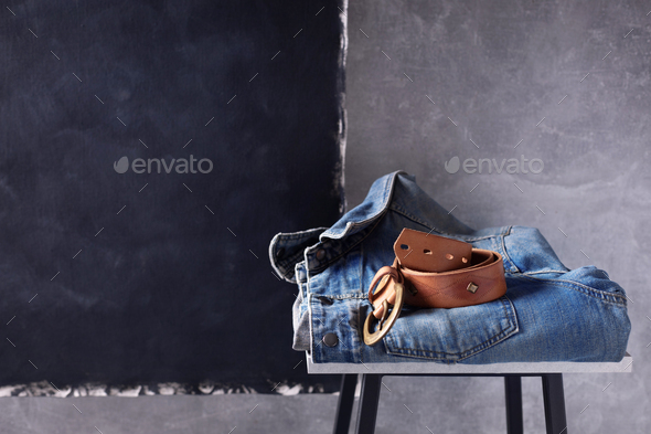 Denim jeans jacket suit and belt at shelf near grey wall background texture - Stock Photo - Images