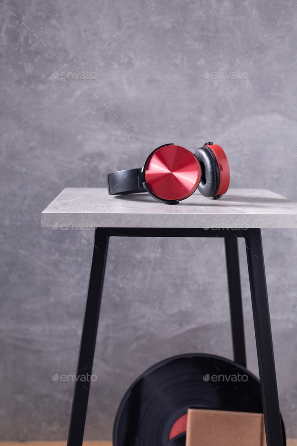 Earphones or headphones at chair near grey wall background texture - Stock Photo - Images