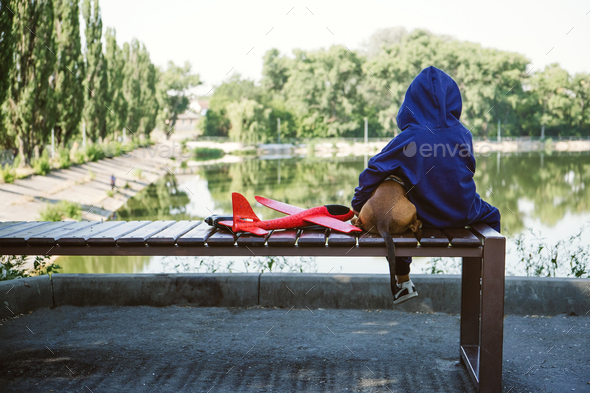Sad kid sitting alone with dog and toy airplane on bench by the river bank. Diagnosing Early-Onset - Stock Photo - Images