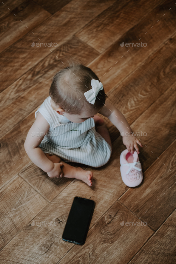 Cute little toddler baby girl with cell phone near on the floor. Vertical portrait of kid sitting on - Stock Photo - Images