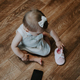 Cute little toddler baby girl with cell phone near on the floor. Vertical portrait of kid sitting on - PhotoDune Item for Sale