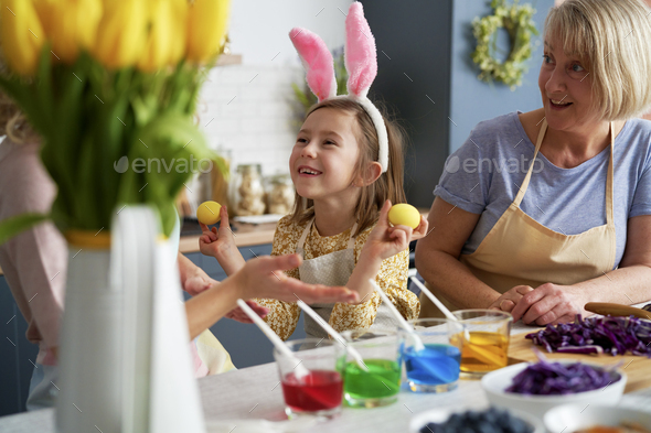 Little girl have fun during coloring Easter eggs with family - Stock Photo - Images