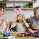 Girl with mother and grandmother have fun during coloring eggs - PhotoDune Item for Sale