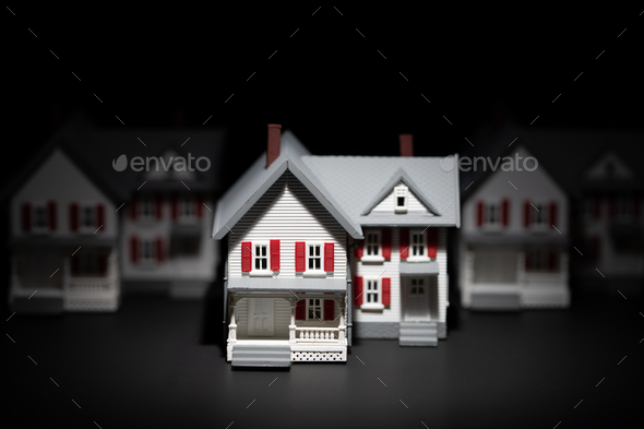 Several Model Houses In A Row With One Spot Lit In The Front - Stock Photo - Images