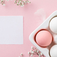 Easter eggs in white ceramic holder and flowers on pink background - PhotoDune Item for Sale